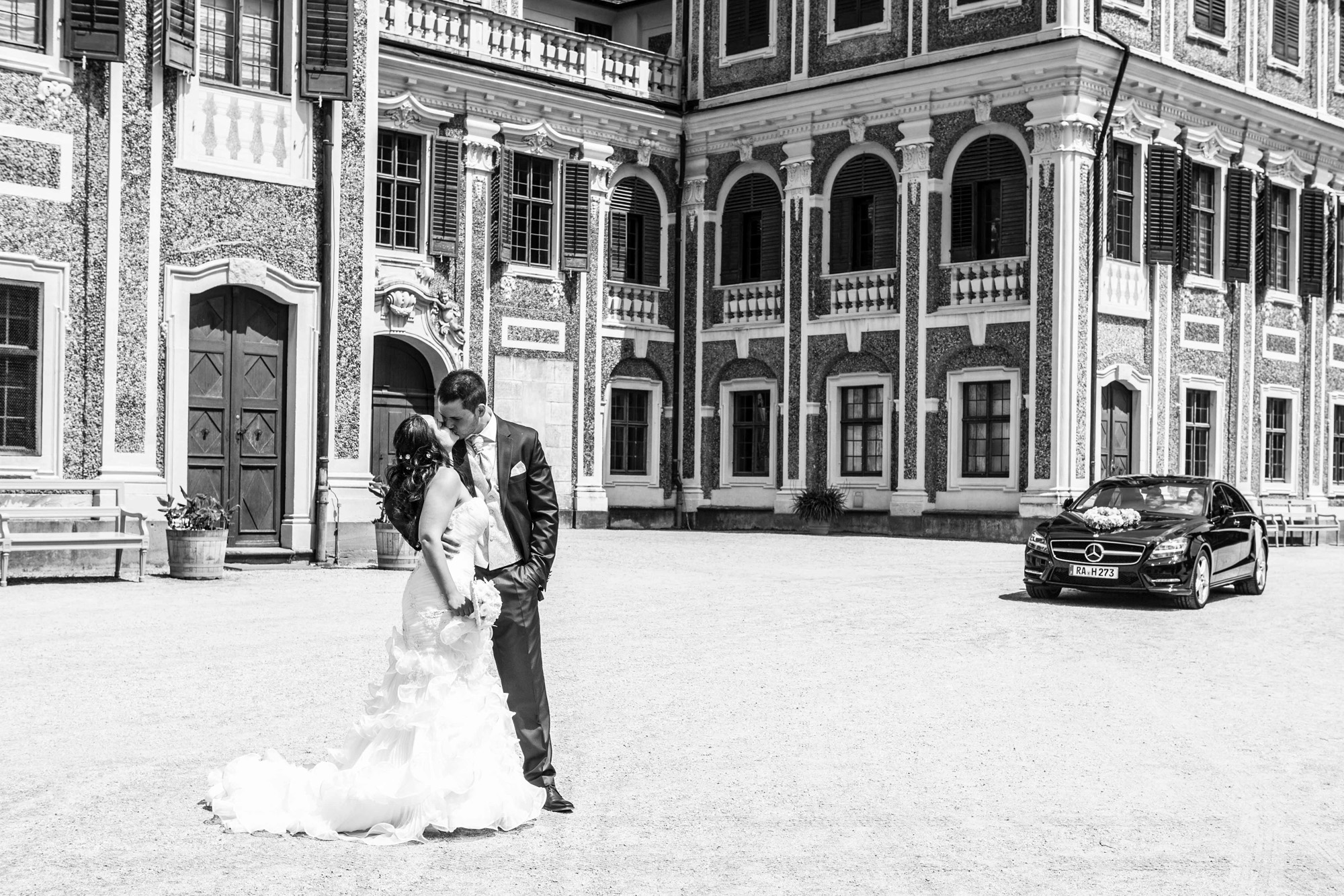 Hochzeitsfotografie - Brautpaar küssend vor dem Schloss