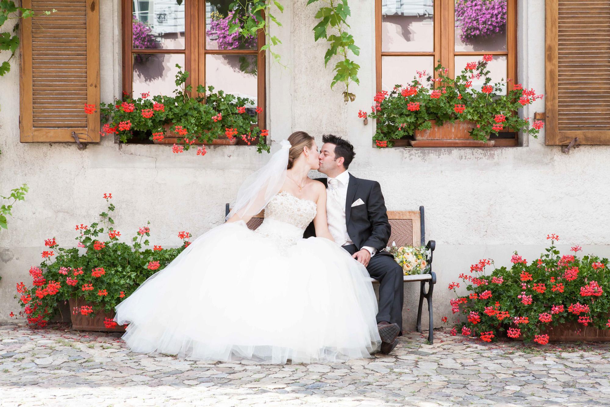 Hochzeitsfotografie - Brautpaar küsst sich auf der Bank